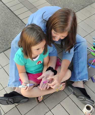 Kiley Bostic, 4, of Beckley, left, gets some help from Laurie Conway, with McDonalds, right, painting her rock, which was used to play hop-scotch with, during Saturday's Kid's festival in downtown Beckley.. F. Brian Ferguson/The Register-Herald