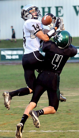 Westside DB Corey Bowles, left, picks off a pass as Wyoming East receiver Christian Hedinger becomes a defender in New Richmond on Friday evening. F. Brian Ferguson/The Register-Herald