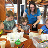 Amy Stover, collection developement programing librarian Raleigh County Library, fourth from left, works with Ian Jenkins, 4, left, Parker Jenkins, 6, Abbie Taylor, 4 and Seth Jenkins, 8, helping making WV I spy bottles at the library.<br /> Rick Barbero/The Register-Herald