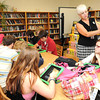 Lovann Broyles, technology coach Raleigh County School Technology Dept., helps Shady Sping High School students set up iPads in the school library.<br /> Rick Barbero/The Register-Herald