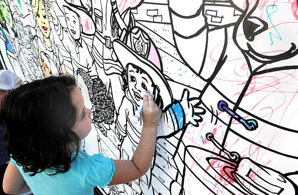 Kara Treadway, 4, of Crab Orchard, provides her artistic touch to a large wall mural during Saturday's Kid's festival in downtown Beckley.. F. Brian Ferguson/The Register-Herald
