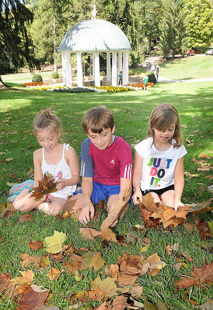 Mallory, 9, Declan, 13 and Kelly Glynn, 9, children of Roty and Meghan Glynn, of Taylor Mill, Ky, play with leaves in front of the spring house at The Greenbrier Resort.<br /> Rick Barbero/The Register-Herald