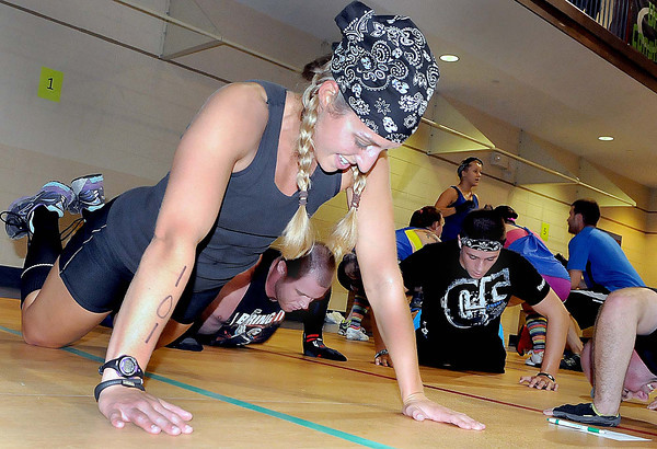 Brittany Drake grinds out some push-ups with her team during Saturday's FOLK program at The Place. Twenty 5-member teams competed to raise money to help feed hungry children. F. Brian Ferguson/The Register-Herald
