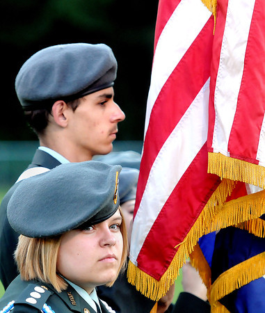 Greenbrier West Junior ROTC members Ashley Johnson, foreground, and Gabe Cecil take the field proudly holding the U.S. colors in Charmco on Friday evening. F. Brian Ferguson/The Register-Herald