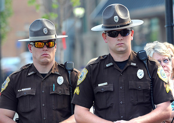 Beckley City Police officers, J.W. Legursky, left, and J.S. Steward, listens to Raleigh County Sheriff Steve Tanner, speak during a 911 ceremony at Jim Word Memorial Park on Neville Street in Beckley Wednesday morning.<br /> Rick Barbero/The Register-Herald