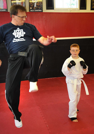 Robert Niday, owner Beckley Martial Arts, left, works with Caleb Williams during his class.<br /> Rick Barbero/The Register-Herald