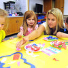 Traci Stacy, third from left, works with Claire Massey, left, Allie Fragile and Dylan Williams, in her pre school class at St. Francis de Sales school.<br /> Rick Barbero/The Register-Herald