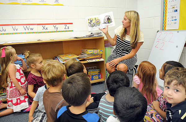 Traci Stacy reads to students in her pre school class at St. Francis de Sales school.<br /> Rick Barbero/The Register-Herald