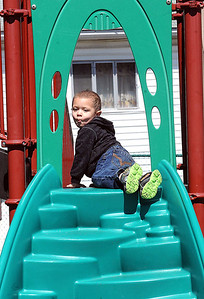 Christian Wilson's, 3, son of Nicole Sherrard, of Beaver, plays on the playground at Thornhill Courts on Second Street in Beckley Monday afternoon. Rick Barbero/The Register-Herald
