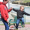 Nicole Sherrard, of Beaver, holds her son Christian Wilson's, 3,  hand, as he attempts to jump of the balancing beam at Thornhill Courts on Second Street in Beckley Monday afternoon.<br /> Rick Barbero/The Register-Herald