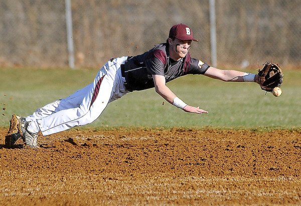 Flying Eagles' second baseman Brandon Chandler dives for a sharply hit ground ball against James Monroe Monday evening at Woodrow Wilson High.<br /> Brad Davis/The Register-Herald