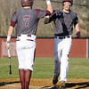 Woodrow Wilson's Hunter Halstead, right, is greeted at the plate by teammate Brent Osborne after both score on a Cameron Lane double down the third base line during the 3rd inning of the Flying Eagles' home win over James Monroe Monday evening.<br /> Brad Davis/The Register-Herald