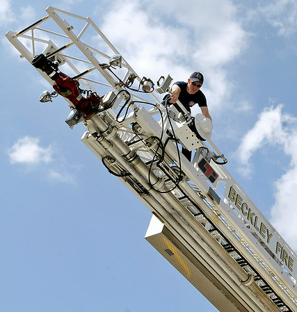 Brad Davis/The Register-Herald   <br /> Beckley firefighter Scott Datsko performs a routine maintenance check high atop Ladder #1 Monday morning in front of Park Middle School. Mondays are the day fire departments throughout the area test and check their equipment for any repairs that might be needed. Station #1, located on 3rd Avenue, brought a couple of their trucks to Park Middle where they'd have some space to extend the massive ladder to make sure it works properly.