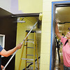 Rick Barbero/The Register-Herald<br /> Kimberlee Walton, left, and Sirena Harper with Lowe's is helping spuce up Stratton Elementary School for the new school year by painting the hallways.
