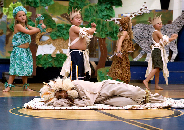 """Brad Davis/The Register-Herald<br /> Playing the role of a Lion, Summer day camper Ram Asaithambi, middle, sleeps as he and fellow Stepping Stones Academy campers dress rehearse scenes from their upcoming musical at St. Francis de Sales Church in Beckley Wednesday afternoon. This year's camp, """"Camp Zulu,"""" is celebrating the cultures and traditions of Africa, culminating with an Awesome Africa musical August 15th."""