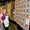 """Brad Davis/The Register-Herald<br /> Quilter Carolyn Mullins looks over her 1st in show ribbon-clad, award winning quilt at right, entitled """"12,000 Pieces,"""" named for literally the 12,000 individual pieces that make up the quilt during the Arts and Crafts Fair August 23 at the Beckley-Raleigh County Convention Center."""