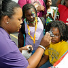 8-year-old Kamya Pannell gets a face painting from Crystal McDonnell while a curious Anijah Atwater (middle), 7, tries to get a closer look as she wears her new backpack during Heart of God Ministries' back to school event Saturday afternoon at the church's South Kanawha Street location. The church handed out school supplies to area children and put on numerous games and entertainment activities.