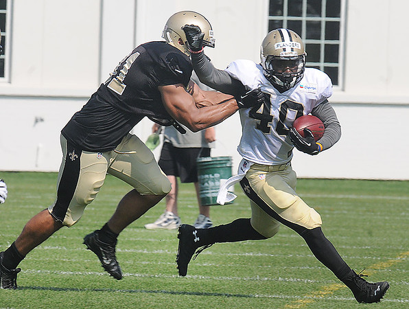 Kasim Edebali, left, tries to tackle Timothy Flanders during the New Orleans Saints practice Tuesday morning at The Greenbrier Resort.<br /> Rick Barbero/The Register-Herald