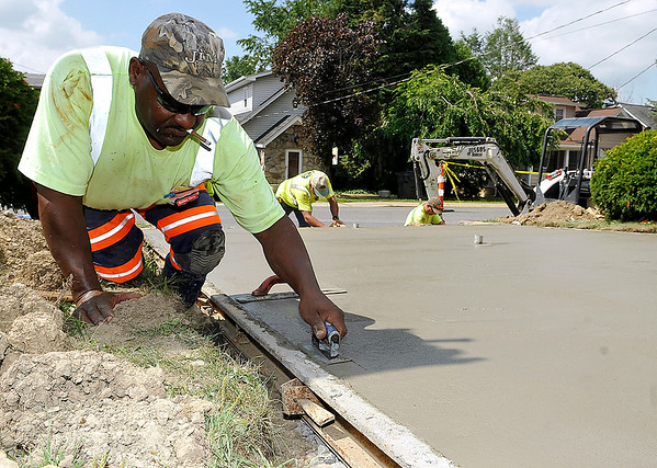Brad Davis/The Register-Herald    <br /> Timmy Wyne (left), construction worker with Jim's Construction out of Charleston, puts a final touch on a brand new concrete walkway that was poured Monday morning at the old school building on Park Avenue. His fellow co-workers Steve Thompson (Middle) and Doug Alderson work on smoothing out the stairs behind him. Raleigh County Schools hired the company to build brand new sidewalks and walkways at the old school building, as well as upgrade several other facilities in the area. For Jim's Construction, it's their sixth project for RCS in the last month.