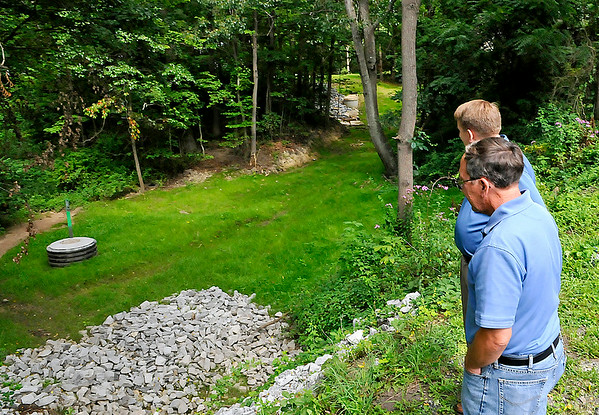 Brad Davis/The Register-Herald       <br /> Beckley Sanitary Board general manager Jeremiah Johnson, left, and operations manager John Peplowski look over a recently finished stormwater drainage project in a low-lying area at the corner of Carter and City Avenues Friday afternoon. The city is in the process of upgrading old, and in some cases dilapidated drainage systems around the city.