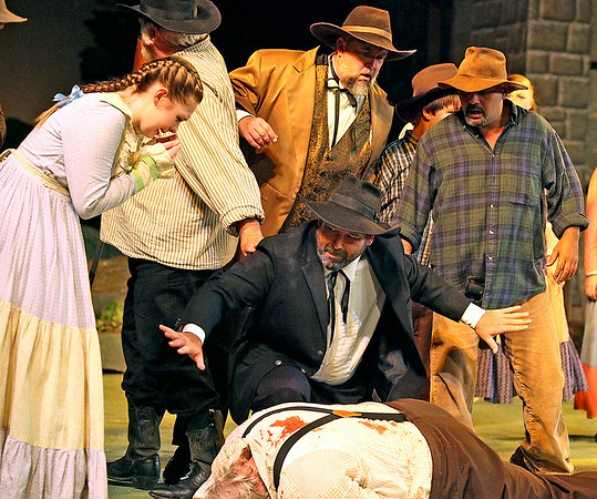 Brad Davis/The Register-Herald<br /> Preacher Anse Hatfield (middle), played by Rocky Cooper, appeals for calm and space as he tends to the gravely wounded Ellison Hatfield (below), played by Rick McNeely, following a fight with the three eldest McCoy sons Tolbert, Phamer and Rand'l Jr. during a pivotal scene of Theatre West Virginia's Hatfields and McCoys July 25 at Grandview Park's Cliffside Amphitheatre. The scene portrays the historic moment that turned the two families' quarrel into a bloody feud.