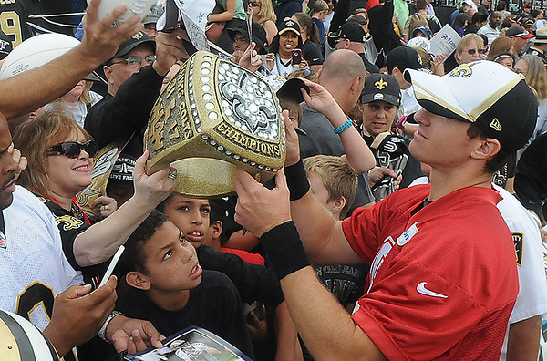 Drew Brees, right, signs autographs after the New Orleans Saints scrimmage Saturday morning at The Grenbrier Resort.<br /> Rick Barbero/The Register-Herald