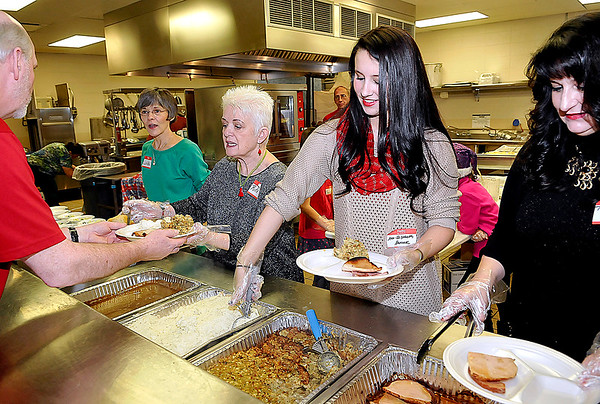 """Brad Davis/The Register-Herald<br /> Volunteers (from left) Linda McCullough, Rita McAlpine, Ann-Elizabeth Hancock and her mother Tammy spend Christmas day preparing plates of delicious hot food for any and all who attended United Methodist Temple's community dinner Thursday afternoon. Hundreds of area residents came out to UMT's """"The Place"""" to enjoy a holiday afternoon with friends, family and a good meal."""