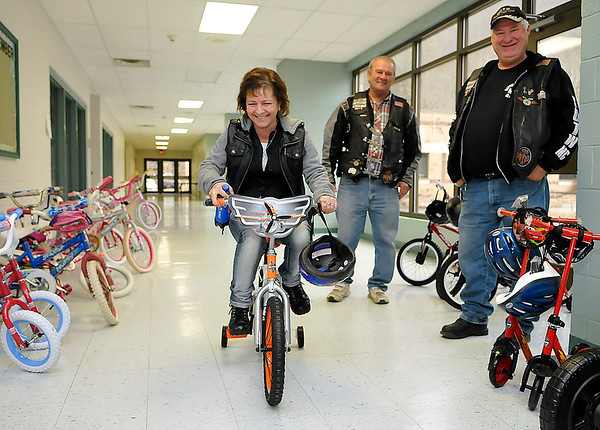 "Brad Davis/The Register-Herald<br /> Tabbatha Bailey decides to test drive one of the brand new bikes she selected for her 6-year-old grandson, much to the amusement of Brothers of the Wheel Motorcycle Club members Paul ""Butch"" Farrington and Sam ""Chub"" Blankenship Sunday morning. The Brothers of the Wheel Southlands Wyoming County branch provided 30 brand new bicycles for boys and girls, purchased from Magic Mart in Oceana thanks to a year-long fundraising effort."