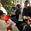 Brad Davis/The Register-Herald<br /> Two-year-old Jalayah Rhodes looks over her new stuffed bear as her grandfather Kermit Rhodes, far right, looks on in amusement Friday afternoon at Valley College.