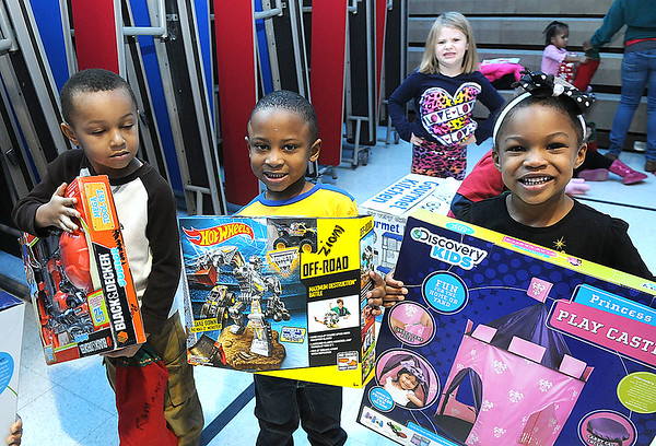 Rick Barbero/The Register-Herald<br /> Ramauri Smith, left, Zion Butcher, Kamya Singleton and Olivia McCoy, all students Town District Head Start Center in Beckley, display gifts presented to them by Santa Claus. Alpha Natural Resources supplied funds for 440 presents that was distributed to all the Head Start programs in Raleigh County.