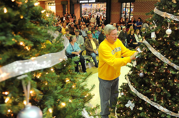 Rick Barbero/The Register-Herald<br /> Hospice of Southern West Virginia celebrated the season with their annual Angel Tree Ceremony Monday at Crossroads Mall. Bob Blackburn, of Oak Hill, places 5 angel ornaments on the tree in memory of his wife, mother, step dad and two brothers.