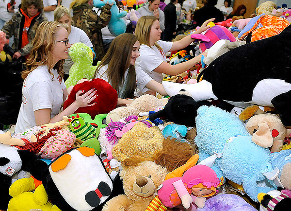 Brad Davis/The Register-Herald<br /> Volunteers (from left) Kenzie Cook, Myleigh Stewart and Cassie Blankenship try to do the impossible task of keeping a massive pile of stuffed animals in an orderly arrangement Sunday morning.