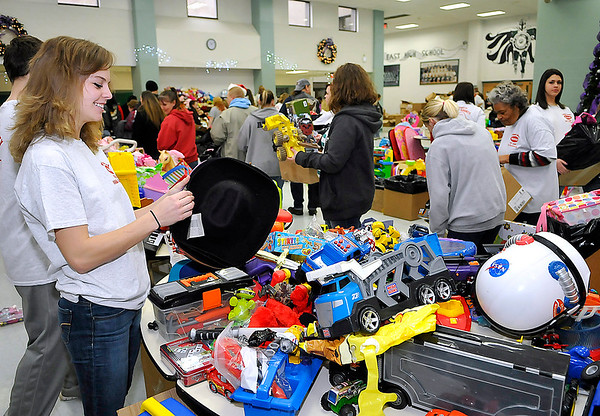 Brad Davis/The Register-Herald<br /> Vulunteer Hope McNeely reflects on years of helping others as she sorts a stack of cowboy hats while working a table loaded with thousands of toys during the Wyoming County Toy Fund party Sunday morning at Wyoming East High School. McNeeley, volunteering for a 10th year, began helping out at the event when she was 8 years old. A graduate of Wyoming East last year, she's now attending Bluefield State College.