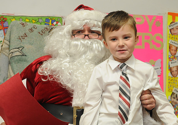 Rick Barbero/The Register-Herald<br /> Santa Claus gave presents to children during a Christmas celebration in Marybeth Garcia's Pre-K class at Crescent Elementay School in Beckley Thursday afternoon.