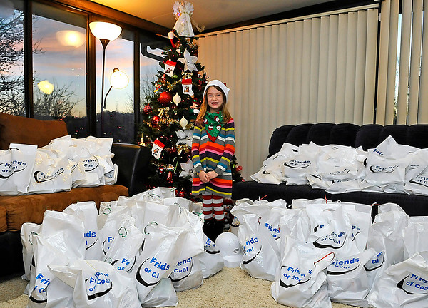 Brad Davis/The Register-Herald<br /> A very proud Tristan Smith, 7, poses for a photo with all the gift bags she'll be giving out to veterans and children for Christmas Thursday evening at her Mabscott home. Smith decided she wanted to give back this Holiday season, so she prepared 139 Christmas cards, all individually hand-signed, for hospitalized veterans at the VA Medical Center and children at the Burlington United Methodist Family Center. Smith is looking for a little help from Santa as well, hoping that he brings her around 65 throw blankets for the veterans. The Friends of Coal Ladies Auxiliary found out about her plan and donated bags of various goodies to go with her cards, and the blankets would complete her plan to spread some Christmas cheer.