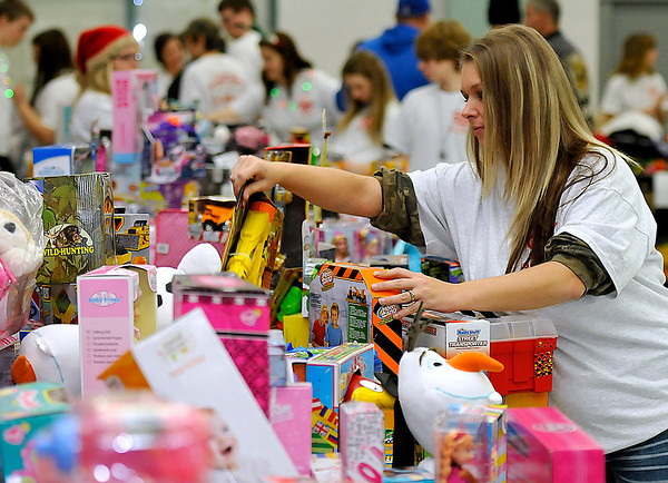 Brad Davis/The Register-Herald<br /> Volunteer Brandi York maintains an orderly mountain of toys during this year's Wyoming County Toy Fund Sunday morning. This was York's 10th year volunteering at the annual event, and it's a family affair with vurtually all of her kin helping out each time as well.