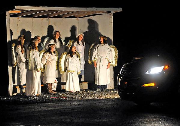 Brad Davis/The Register-Herald<br /> Angels sing as motorists enjoy Cranberry Baptist Church's Living Christmas Story Friday night.