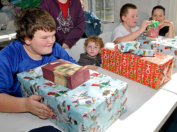 Brad Davis/The Register-Herald<br /> Youngters (from left) Isaiah Adkins, 12, Myles Cook, 3, and Isaiah's brother Elijah, 11, wait with enthusiasm to open their presents as the Adkins' mother Brenda Crider, far right, looks on Sunday afternoon at the Pine Haven Center. A handful of lucky children at the center received Christmas presents Sunday from the Alfred A. Torres Memorial Toy Fund, named after a Beckley native and former Marine who passed away in 2013 and had a special place in his heart for the area's youth. His wife Ann started the fund in his honor, aiming to provide Christmas presents for any child that otherwise wouldn't have any, and Flat Top Arms owners Ron Diana Wood chipped in to help provide the group of kids a very merry Christmas.