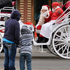 Brad Davis/The Register-Herald<br /> Sophia youngsters Yamir Mayo (right), 5, and Faith Charlden, 14, draw waves from Santa and Mrs. Claus during the town's Christmas parade along Main Street Saturday afternoon.