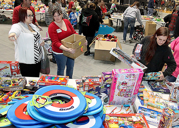 Brad Davis/The Register-Herald<br /> Beckley resident Caressa Browning, far left, shops with the help of volunteer Trish Tolliver while another shopper at right browses thousands of items available at Mac's Toy Fund Party Saturday morning at the Beckley-Raleigh County Convention Center.