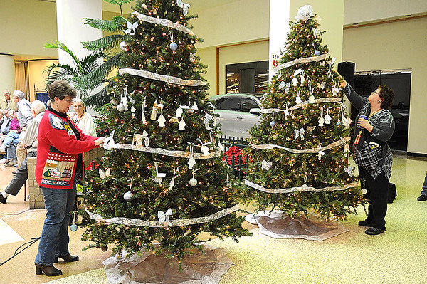 Rick Barbero/The Register-Herald<br /> Hospice of Southern West Virginia celebrated the season with their annual Angel Tree Ceremony Monday at Crossroads Mall. Dorinda Taylor, of Victor, left, places angel ornaments for her parents and Pam Sodosky, of Beckley, places on for her mother and grandmother.