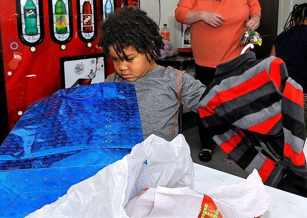 Brad Davis/The Register-Herald<br /> Four-year-old O'Syrus Moore opens his gifts Sunday afternoon at the Pine Haven Center. A handful of lucky children at the center received Christmas presents Sunday from the Alfred A. Torres Memorial Toy Fund, named after a Beckley native and former Marine who passed away in 2013 and had a special place in his heart for the area's youth. His wife Ann started the fund in his honor, aiming to provide Christmas presents for any child that otherwise wouldn't have any, and Flat Top Arms owners Ron Diana Wood chipped in to help provide the group of kids a very merry Christmas.