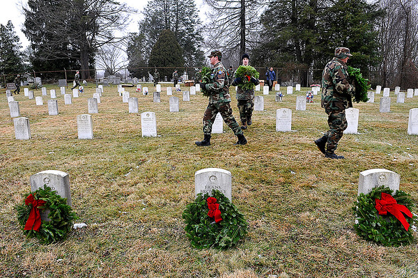 Brad Davis/The Register-Herald<br /> Lieutenant Colonel David Chaney, right, Cadet Airman First Class Ethan Lafferty, left, and Cadet Airman First Class Matthew Smith (middle), members of the West Virginia Civil Air Patrol's Beckley Composite Squadron carry wreaths to be placed on the graves of every service member buried at the American Legion Cemetery off South Kanawha Street following a ceremony Saturday morning. The event was part of Wreaths Across America's nationwide effort to honor and remember the country's fallen service men and women with a holiday wreath. Mountaineer Automotive Group, The Beckley Moose Lodge and the Beckley Mountaineer Auto Mall donated funds for the 189 wreaths laid Saturday.