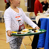 Brad Davis/The Register-Herald<br /> Young volunteer Laken Jarrell, 7, patrols the dining area inside The Place with a tray full of desserts Christmas day at United Methodist Temple.