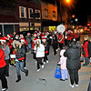 Brad Davis/The Register-Herald<br /> Collins Middle School's Little Red Devil Marching Band makes its way along Main Street in Oak Hill as spectators line the streets during the city's Christmas parade Thursday night.