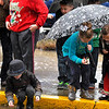 Brad Davis/The Register-Herald<br /> Youngsters scramble to rescsue uncaught candy from the streams of water running along the streets of Beckley during a soggy Christmas Parade Saturday afternoon.