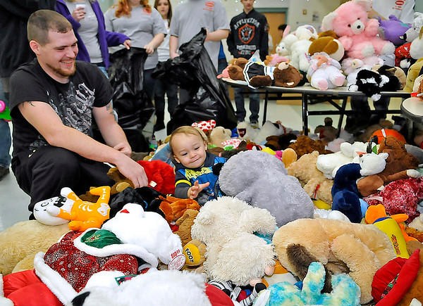 Brad Davis/The Register-Herald<br /> Steven Hash, left, has a laugh as he keeps an eye on his 17-month-old Keevin, who is having a blast trying out all the hundreds of different stuffed animals available at the Wyoming County Toy Fund Sunday morning at Wyoming East High School. The younger Hash, unable to determine which stuffed animal he liked the best, decided he liked the entire pile rather than just one.