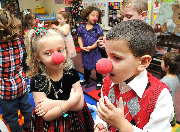 Rick Barbero/The Register-Herald<br /> Lily Garcia, left and Tryston Torres-Ayres, put on red noses preparing to sing Rudolph the Red Nosed Reindeer during a Christmas celebration in Marybeth Garcia's Pre-K class at Crescent Elementay School in Beckley Thursday afternoon.