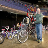 Brad Davis/The Register-Herald<br /> Volunteer George Barbera double-stacks a pair of bicycles as he wheels them out to a shoppers car  during Mac's Toy Fund Party Saturday morning at the Beckley-Raleigh County Convention Center.