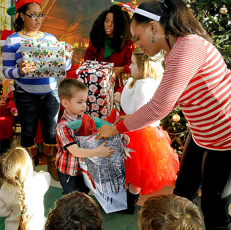 Brad Davis/The Register-Herald<br /> Four-year-old Lucas Burnside gets a gift from Valley College's director of academics Juanita Acheampong during a visit from Santa at the school Friday afternoon.